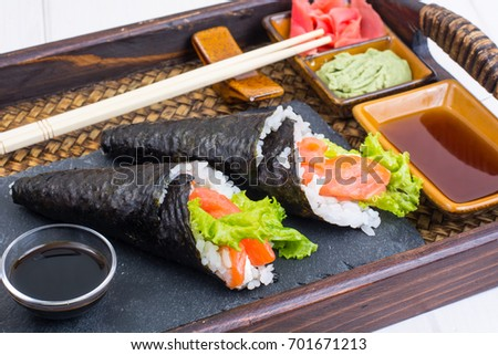 Salmon temaki sushi cone on the tray. Studio Photo