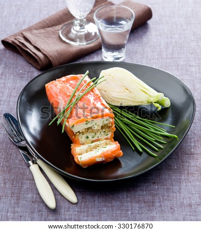 Salmon Terrine with Fennel smoke on the elegant black plate with green onions on a tablecloth made of linen - stock photo