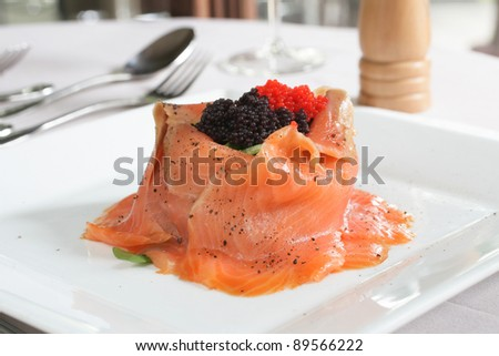 Salmon volcano salad with rocket, topped with red and black caviar