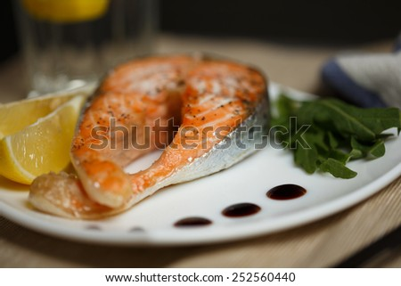 Salmon with a balsamic vinegar sauce , fresh salad and lemon  - stock photo