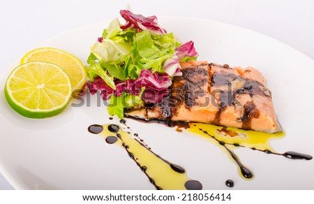 Salmon with a reduction of balsamic vinegar and sugar, fresh salad, lemon lime - stock photo