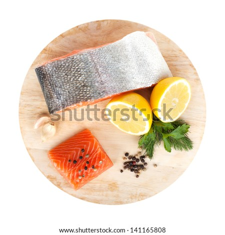 Salmon with herbs and lemon slices on cutting board. Isolated on white background - stock photo