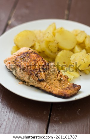 Salmon with potatoes on white plate