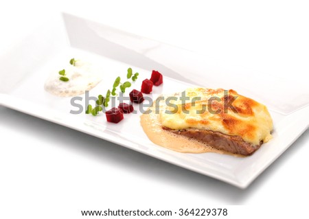 salmon with white sauce, herbs and braised cauliflower on white plate isolated on white background, product photography for restaurant, DOF