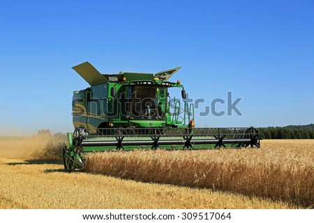 SALO, FINLAND - AUGUST 22, 2015: John Deere Combine s670i harvests barley at Puontin Peltopaivat Agricultural Harvesting and Cultivating Show. - stock photo