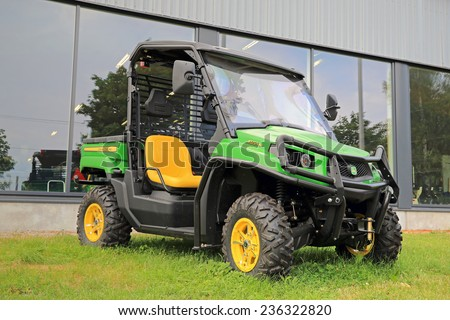 SALO, FINLAND - AUGUST 9, 2014: John Deere Gator XUV550 Crossover Utility Vehicle on grass. The Gator has a V-twin engine and independent four-wheel suspension. - stock photo