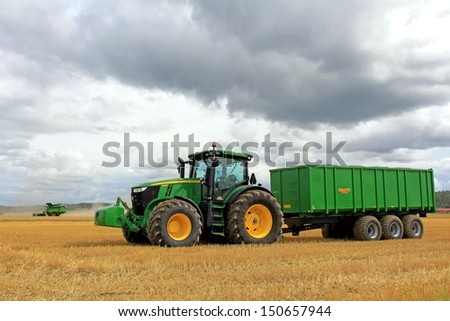 SALO, FINLAND - AUGUST 10: John Deere 7280R tractor with trailer and combine harvester at the annual Puontin Peltopaivat Agricultural Harvesting and Ploughing Show on August 10, 2013 in Salo, Finland - stock photo