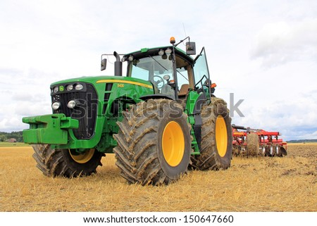 SALO, FINLAND - AUGUST 10: John Deere 8430 Tractor and Vaderstad Cultivator on display at the annual Puontin Peltopaivat Agricultural Harvesting and Ploughing Show on August 10, 2013 in Salo, Finland. - stock photo