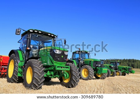 SALO, FINLAND - AUGUST 22, 2015: Line up of four John Deere agricultural tractors, 6115R and 7340 on the left, at Puontin Peltopaivat Agricultural Harvesting and Cultivating Show. - stock photo