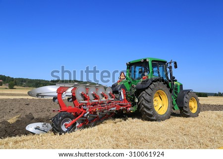 SALO, FINLAND - AUGUST 22, 2015: Unnamed farmer operates John Deere 6630 tractor and Agrolux plow on field at Puontin Peltopaivat Agricultural Harvesting and Cultivating Show. - stock photo