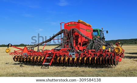 SALO, FINLAND - AUGUST 21, 2015: Vaderstad Spirit 600C Seed Drill and John Deere 7340 tractor on field at the set up of Puontin Peltopaivat Agricultural Harvesting and Cultivating Show. - stock photo