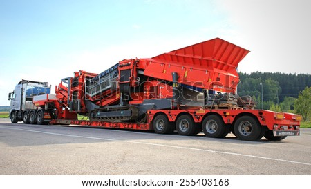 SALO, FINLAND - AUGUST 18, 2013: Volvo FH hauls Terex Finlay tracked mobile jaw crusher on double drop deck trailer. Jaw crushers are used for reducing and sizing aggregates for construction material. - stock photo