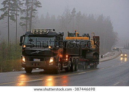 SALO, FINLAND - FEBRUARY 6, 2016: Volvo FM truck hauls a Volvo crawler excavator on a foggy winter evening in South of Finland.  - stock photo