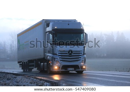SALO, FINLAND - JANUARY 1, 2017: Silver Mercedes-Benz Actros 1845 semi transports Bring cargo trailer along road on a foggy winter evening.