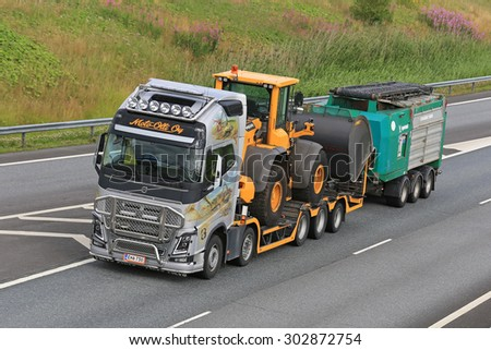 SALO, FINLAND - JULY 31, 2015: Volvo FH hauls a Volvo Wheel loader and Crambo 5000 wood shredder. Crambo 5000 is a dual-shaft shredder for all types of wood and green waste. - stock photo