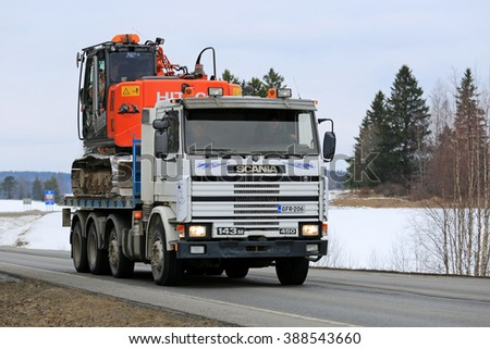 SALO, FINLAND - MARCH 4, 2016: Scania 143M 450 flatbed truck hauls Hitachi Crawler excavator at spring. Scania 3-series trucks were produced from 1987 to 1997.  - stock photo