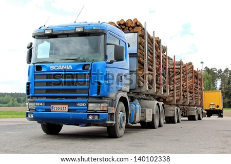 SALO, FINLAND - MAY 25, 13: A Scania 420 logging truck in Salo, Finland on May 26, 13. In Finland, the demand for timber stays high, and weekly sales are soon expected to reach 1 Million cubic metres. - stock photo