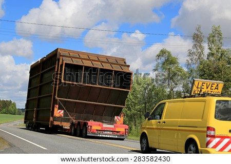SALO, FINLAND - MAY 31, 2015: Escort cars accompany an exceptional load transport along highway. On Finnish roads at least one escort vehicle is necessary, if the load exceeds 3,5 m in width. - stock photo