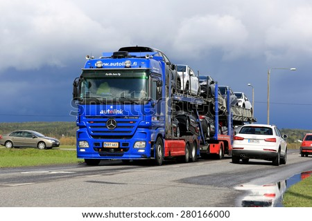 SALO, FINLAND - MAY 15, 2015: Mercedes-Benz Actros car carrier hauls new cars. The Finnish automotive industry estimates that a total of 109,000 new passenger cars will be sold in Finland in 2015. - stock photo