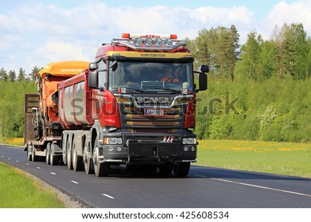 SALO, FINLAND - MAY 20, 2016: New Scania truck transports roadworks equipment along rural spring highway in South of Finland. - stock photo