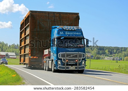 SALO, FINLAND - MAY 31, 2015: Volvo FH truck hauls a wide load along highway accompanied by escort cars. On Finnish roads at least one escort vehicle is necessary, if the load exceeds 3,5 m in width. - stock photo