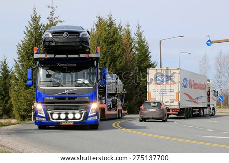 SALO, FINLAND - MAY 1, 2015: Volvo FM carrier hauls a load of new cars. The Finnish automotive industry estimates that a total of 109,000 new passenger cars will be sold in Finland in 2015. - stock photo