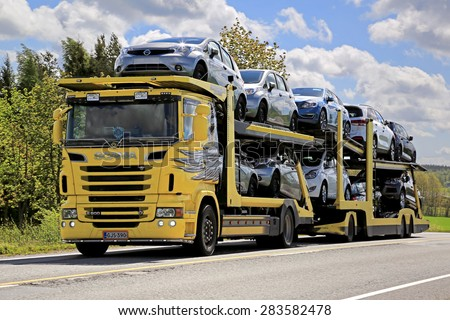 SALO, FINLAND - MAY 31, 2015: Yellow Scania R500 truck hauls a load of new cars. The Finnish automotive industry estimates that a total of 109,000 new passenger cars will be sold in Finland in 2015. - stock photo