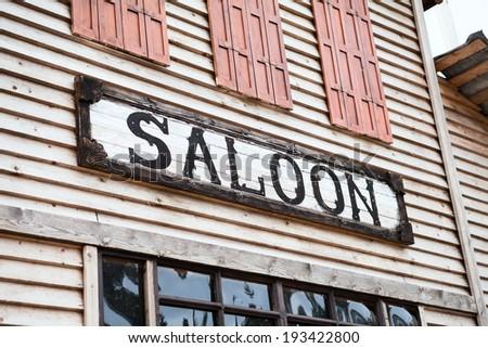 Saloon sign on building facade - stock photo