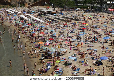 SALOU, SPAIN - JUNE 22: People relaxing and having fun on the beach to have their holidays on June 22, 2014 at the coast of Salou, Spain, a famous tourist destination