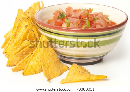 Salsa dip with tortilla chips. Coarsely chopped dip in a bowl surrounded by tortillas isolated on white.