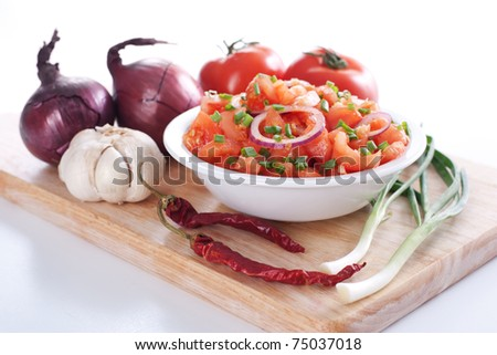 Salsa in a bowl on a wooden board and the ingredients: tomatoes, onions, garlic, chili pepper - stock photo