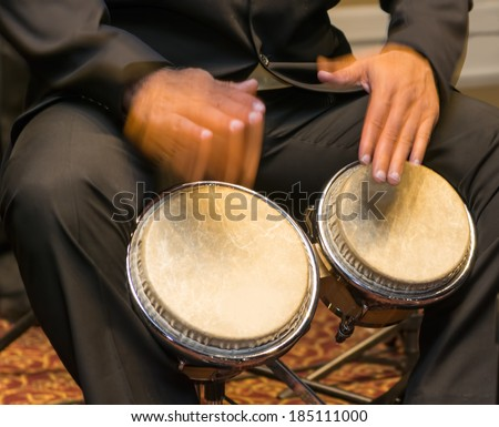 Salsa musician playing the bongos, a percussion instrument traditional for the Caribbean and Latin American music - stock photo