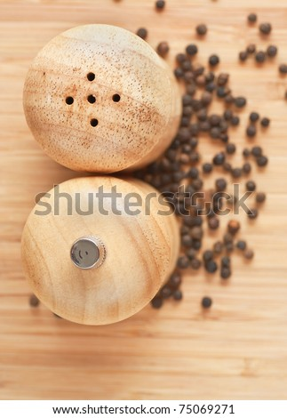 salt and pepper grinders on a table, with pepper spread around