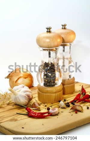 salt and pepper mill with ingredients around on wooden cutting board on a white background - stock photo