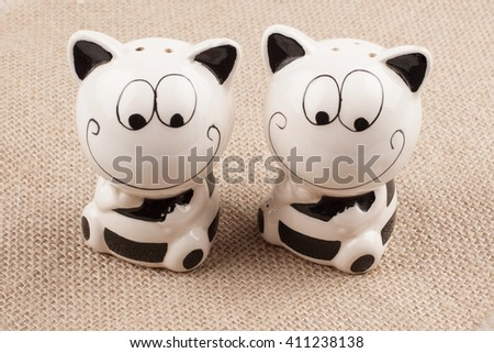 Salt and pepper. Seasoning to the dishes. Funny tableware. The salt and pepper in the shape of cats on linen background - stock photo