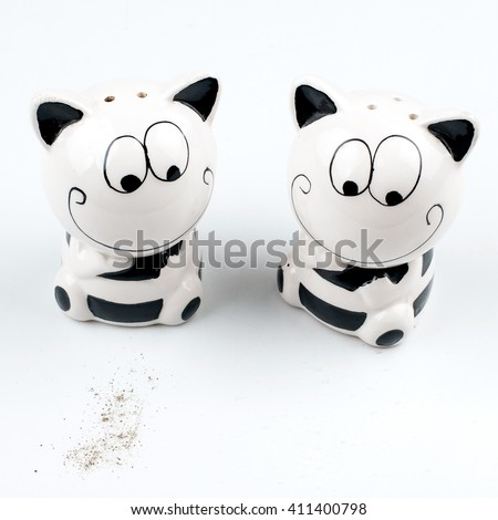 Salt and pepper. Seasoning to the dishes. To spill salt. Waking pepper. The salt and pepper in the shape of cats on white background - stock photo