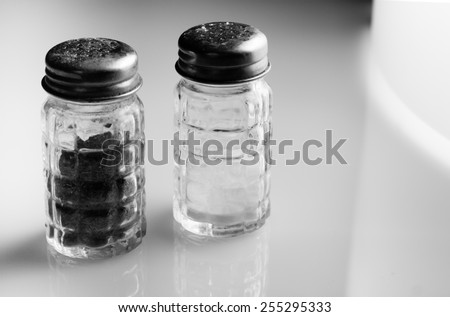 Salt and pepper shakers on shiny surface