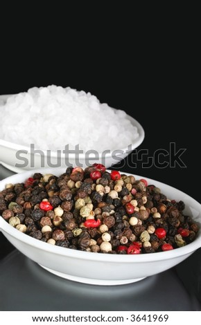 Salt and Pepper.  Small white dishes of peppercorns and coarse seasalt.