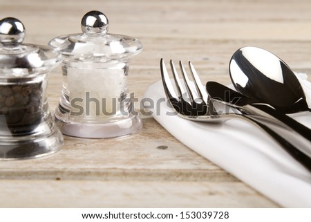 Salt and pepper with fork, knife and spoon on napkin - stock photo