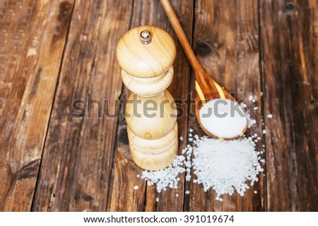 Salt and salt mill on wooden table. Front focus - stock photo