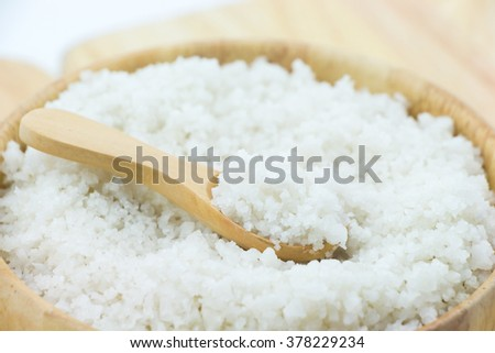 Salt and wooden spoon in wooden bowl