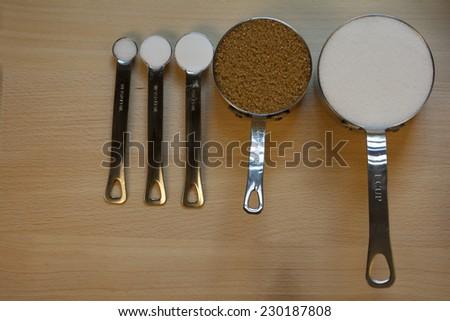 Salt,Baking Soda,Baking Powder in Measuring Spoons and Sugar in Measuring Cup - stock photo