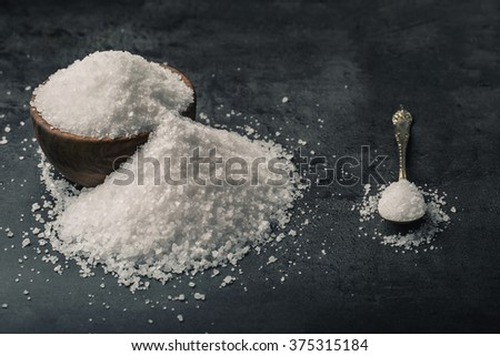 Salt. Coarse grained sea salt on granite - concrete  stone background with vintage spoon and wooden bowl.