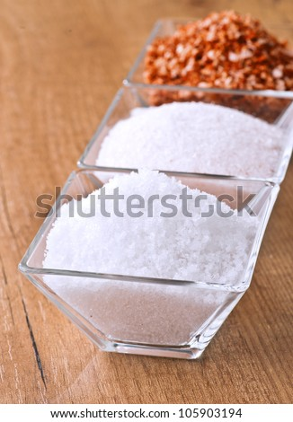 salt flakes in small bowl of glass. Behind salt spices and salt Hymalaya - stock photo