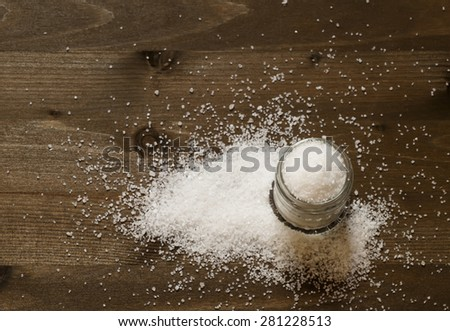 Salt in a glass jar on a wooden background, top view, selective focus