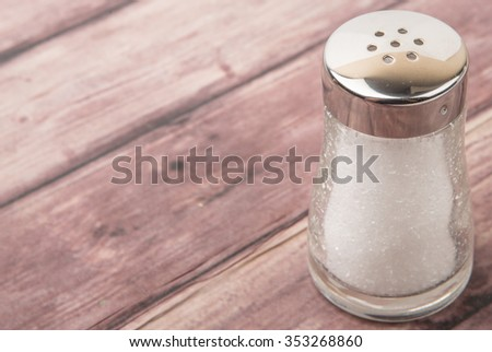 Salt in glass condiment shaker over wooden background - stock photo