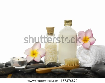 salt in glass, frangipani, towel ,candle on wet black pebbles
