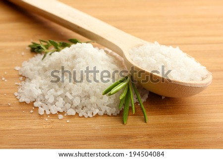 salt in spoon with fresh  rosemary and thyme on wooden background