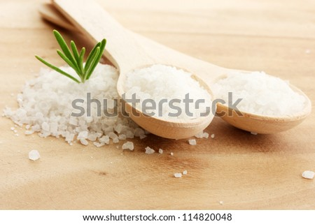 salt in spoons with fresh  rosemary on wooden background - stock photo