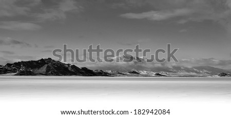 Salt Lake frozen over in winter, with a snow capped mountain in the background. - stock photo